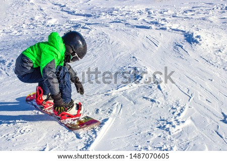 Kid on snowboard in winter sunset nature. Sport photo with edit space #1487070605