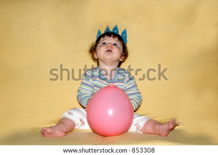 Kid on the sofa looking at... the balloons?... at the ceiling, while wearing a crown and holding a balloon.