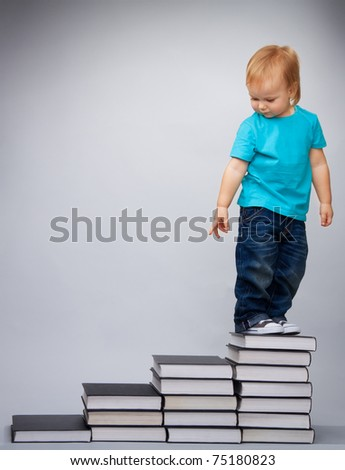 Kid on top of early education leader made of pile of books standing and looking back