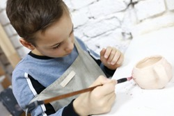 Kid painting clay pot in pottery workshop
