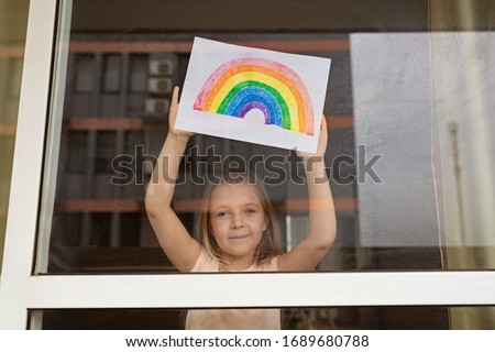 Kid painting rainbow during Covid-19 quarantine at home. Girl near window. Stay at home Social media campaign for coronavirus prevention, let's all be well, hope during coronavirus pandemic concept