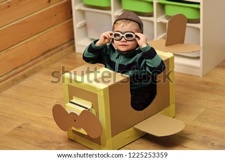 Kid, pilot school, innovation. Air mail delivery, aircraft construction. Dream, career, adventure, education. Little boy child play in cardboard plane, childhood Pilot travel airdrome imagination