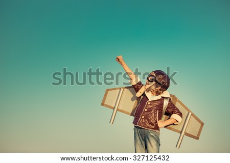 Kid pilot with toy jetpack against autumn sky background. Happy child playing outdoors