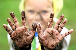 Kid play in a garden and show dirty muddy hands.