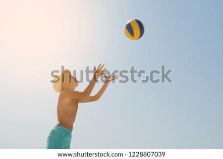 Kid play volleyball on sea beach, against sunny sky background