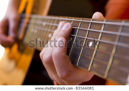 Kid playing acoustic   guitar close-up