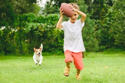 Kid playing American football ready to make touchdown and dog chasing him