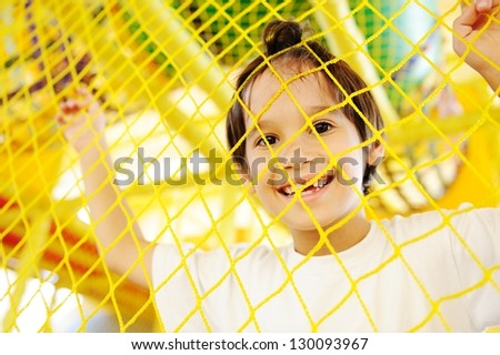 Kid playing at new playground kindergarten behind the net