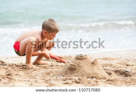 Kid playing at the beach, building sand castle