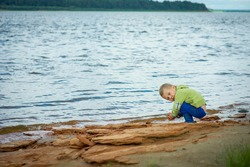 kid playing in the sand and with cameos on the riverbank, selective focus