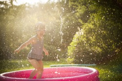 kid playing in water during summertime