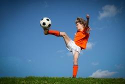 kid playing soccer kicking football