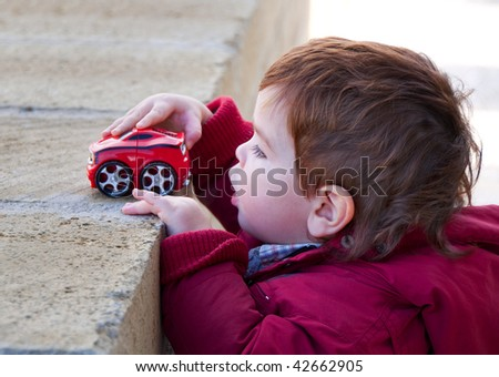 Kid playing with a red toy car