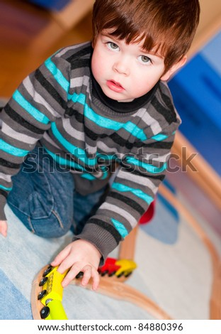 Kid playing with a toy train indoors