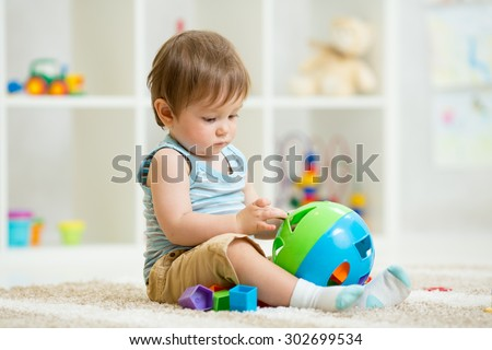 kid playing with logical toy on soft carpet in children room