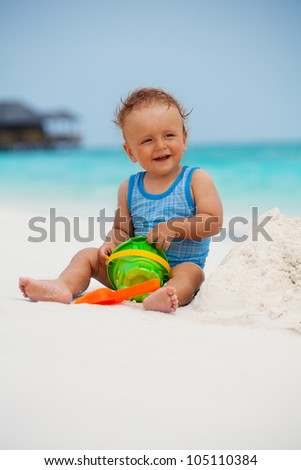 Kid playing with sand sitting on the Maldivian beach