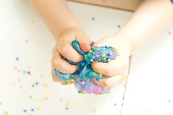 Kid plays with a radiation slime filled with tiny foam beads.  The concept of a happy and fun childhood.