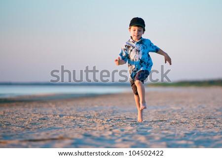 Kid Runs On The Beach at sunset - stock photo