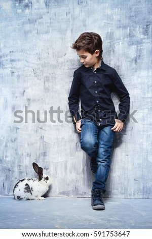 Kid's fashion. Modern nine year old boy posing with rabbit. Clothes for children. Easter holidays.