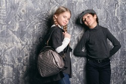 Kid's fashion. Two modern children are posing together on grunge background at at the studio. Clothes for children.
