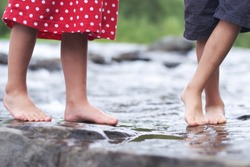 Kid's feet wading in shallow water