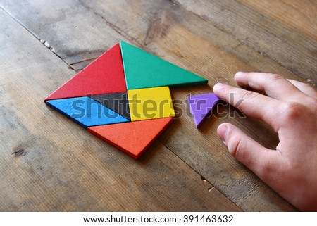 kid's hand holding a missing piece in a square tangram puzzle, over wooden table.  #391463632