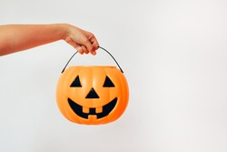 Kid's hand holding Jack'O pumpkin basket to collect candy trick or treat on Halloween day. Concept for Halloween holiday.