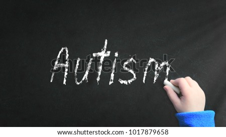 Kid's hand writing with a chalk on a blackboard in the classroom the word autism. Psicology concept. Foto stock ©