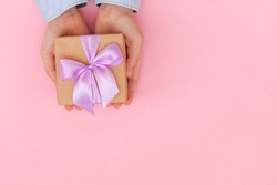 Kid's hands holding gift box wrapped in craft paper and tied with bow on pink background. Concept Mother's Day or Birthday greeting card.