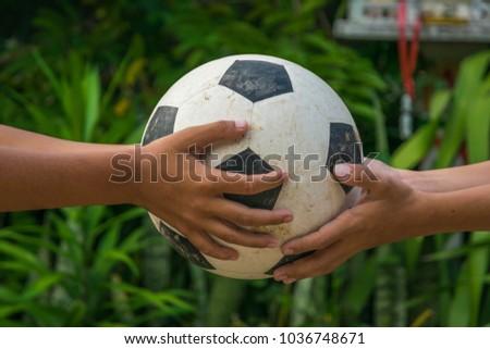 Kid's hands holding old football Stock fotó ©