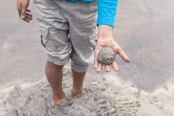 Kid's hands with river mud. Fun childhood game. Research nature. Happy young boy in mud playing outside in the river on a summer day.