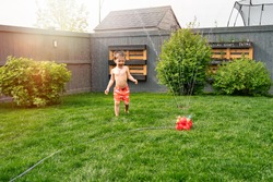 Kid's outdoor activity. Funny toddler boy wearing a orange swimming shorts running and jumping around garden sprinkler playing with water splashes having fun in the backyard on a sunny hot summer day.