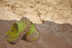 Kid's sandals on the sand beach
