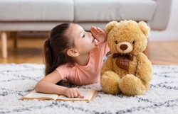 Kid's Secrets. Little Asian Girl Reading Book Whispering Sharing Secret With Teddy Bear Playing Lying On Floor At Home.