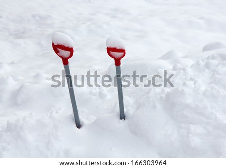 Kid's shovels left in the snow bank before a snowfall