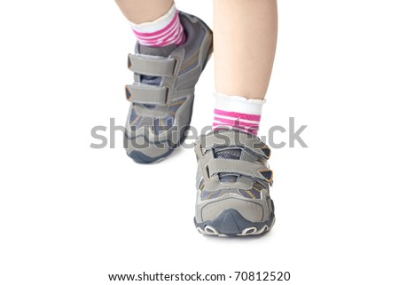 Kid`s sneakers. Closeup of child legs wearing shoes. Isolated on white background.