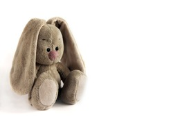 Kid's toy plush hare sitting on a white background. Soft toy for a child. Grey rabbit with a pink nose, isolated on white.