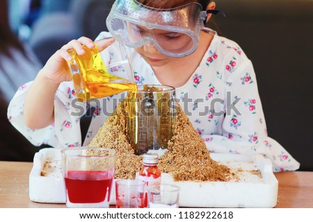 Kid science experiment of volcano or Baking Soda and Vinegar Volcano Eruption for Kid.Girl with eyeglasses pouring dish soap to the  container of baking soda,mixed and poring vinegar for volcano labs.