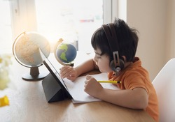Kid self isolation using tablet for his homework,Child doing using digital tablet searching information on internet while school of during covid-19 lock down,Social Distance, learning online education