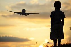 Kid silhouette on meadow looking at airplane in air