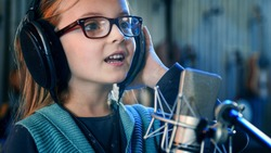 Kid singing in studio.Little girl singing a song.Front view close up. Kid wearing headphones attending singing class.
