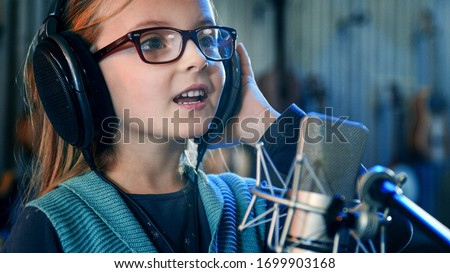 Kid singing in studio.Little girl singing a song.Front view close up. Kid wearing headphones attending singing class. Stockfoto ©