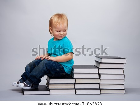 Kid sitting on a a steps made of books and laughing
