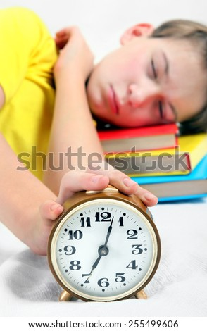 Kid sleep with Alarm Clock on the Bed. Focus on the Clock