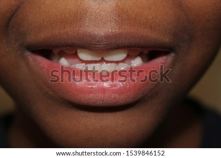 Kid Smile showing teeth and half smiling #1539846152