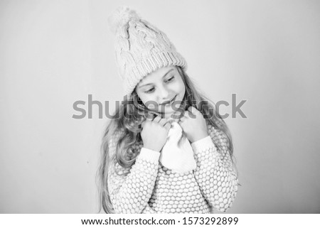 Kid smiling wear knitted accessory. Kid girl wear cute knitted fashionable hat and scarf accessory. Winter fashion accessory. Winter accessory concept. Girl long hair dreamy mood pink background.