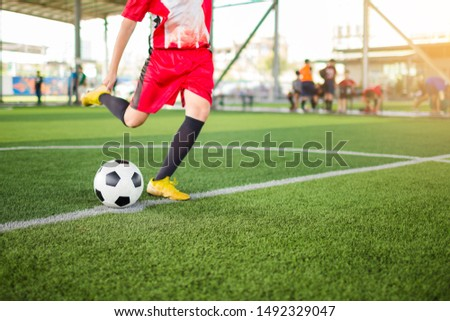 kid soccer player shoot ball to goal on artificial turf with blurry soccer player background. Soccer player training in football academy.