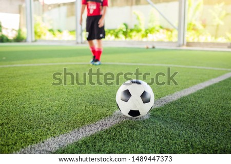 kid soccer player speed run to shoot ball to goal on artificial turf with blurry soccer player background. Soccer player training in football academy.