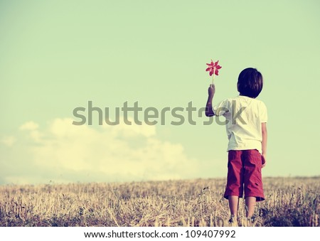 kid standing in nature with...