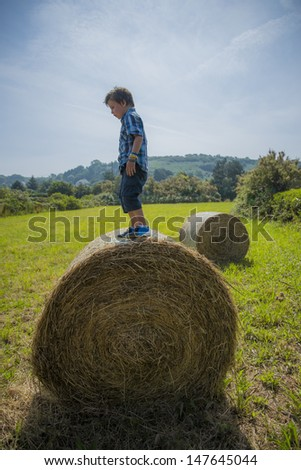 kid standing on a round hay bale,looks like he's balancing on it